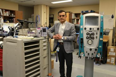 Dr. Robert Apardian, Chief of Biomedical Engineering and Medical Physics, with a medication dispensing trolley adapted by his team.