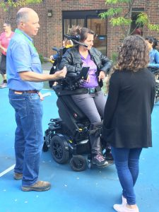 Daniel Rock, a Wheelchair Positioning Technician from Constance Lethbridge, introduces Occupational Therapist Diane Bouchard of CLSC Saint-Henri to a motorized wheelchair with specialized controls and standing frame.