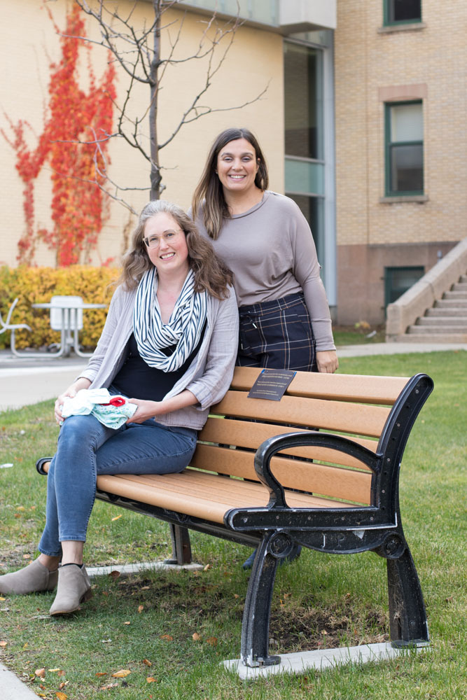 Nurse Nadine Fava (seated) and Social Worker Louna Kadoch, Co-Chairs of the Perinatal Loss Committee at the JGH, holding clothing items they place in Memory Boxes, a symbolic keepsake given to parents at the time of their loss. The commemorative bench and a nearby sapling were dedicated in 2017.