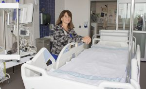 Jacki Raboy Thaw debout devant un lit thérapeutique semblable à celui transporté de l'HGJ à l'Hôpital Mont-Sinaï pour combler le vœu Moments magiques d'une patiente de l'Unité des soins intensifs.