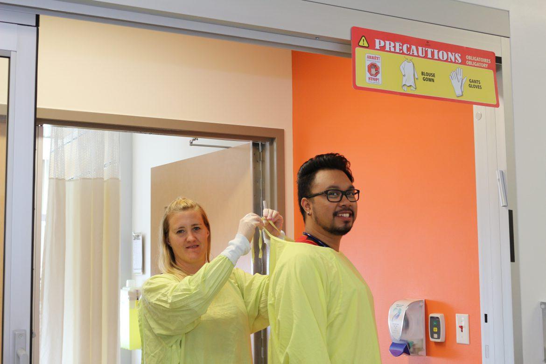La conseillère cadre en Soins infirmiers, Stéphanie Maynard, et l'infirmière Kirby Montecillo, respectent les PA « jaunes » de prévention des infections en enfilant une blouse et des gants dans l'Unité de neuroscience, au pavillon K de l'HGJ.