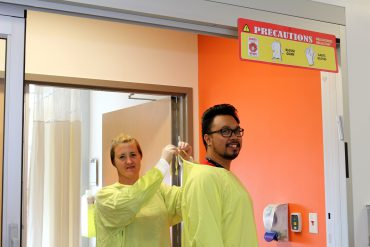Nursing Clinical Consultant Stephanie Maynard and Nurse Kirby Montecillo follow AP 'yellow' precautions, donning their gowns and gloves on the Neuroscience Unit in Pavilion K.