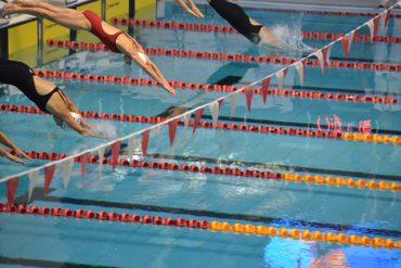 La Dre Klam plonge dans l'eau. Les deux médecins arboraient un maillot de bain rouge pour représenter le Canada.