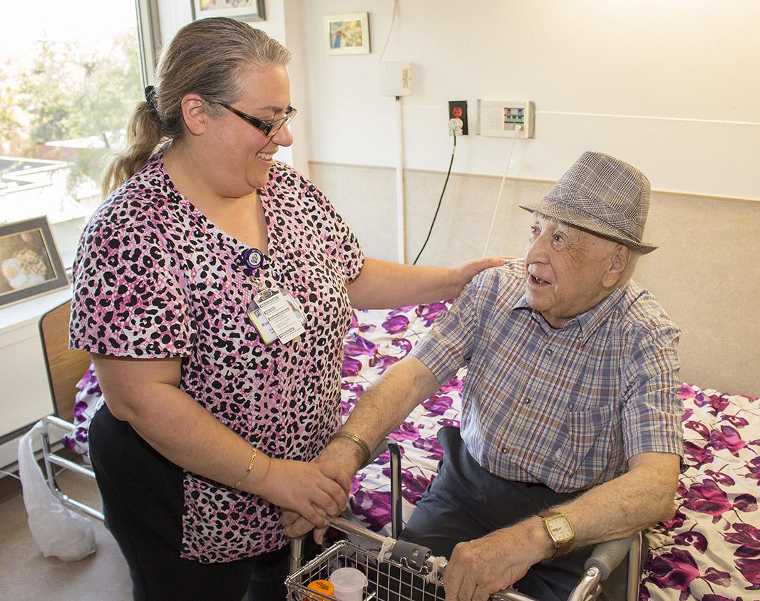 Au CHSLD juif de Montréal, l'infirmière Donna Koutsandreas s'assure que le résident Marcel Scheinfeld est prêt à se lever et à utiliser sa marchette.