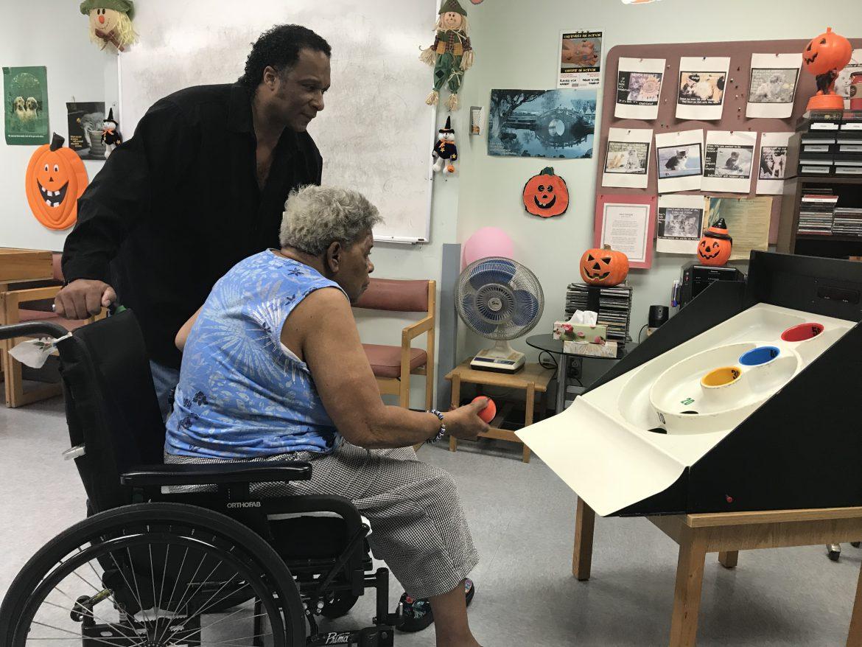 Ray Cassel aide la résidente Joan Oliver pendant une partie de jeu de poches au Centre d'hébergement Father-Dowd.