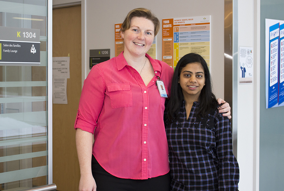 Susan Cameron (à gauche), infirmière-enseignante au sein de l'Unité des soins intensifs médicaux-chirurgicaux, est en compagnie de l'étudiante bénévole Rabbia Akhtar-Tariq devant le salon des familles de l'USIMC, où des bénévoles accueillent les visiteurs et les guident au sein de l'Unité.