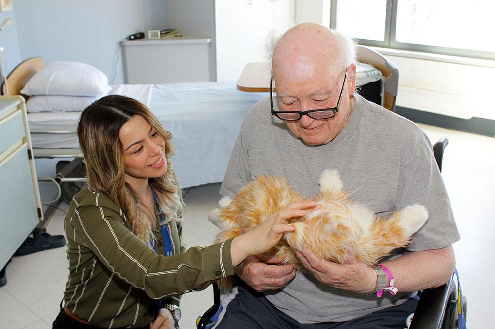 Sabrina Cabral, technicienne en loisirs au CHSLD juif Donald Berman, et Gordon Lyons, un résident, jouent avec un chat robotisé.