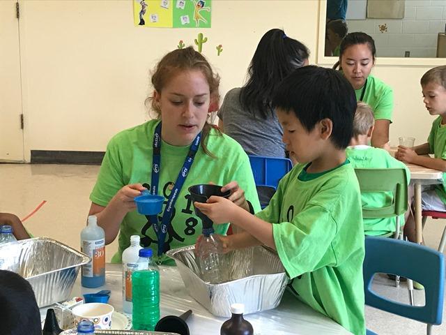 Une employée de Lethbridge-Layton-Mackay aide un campeur pendant une activité de science au Camp pour les enfants atteints de trouble développemental de la coordination tenu en 2018 à l'établissement Mackay