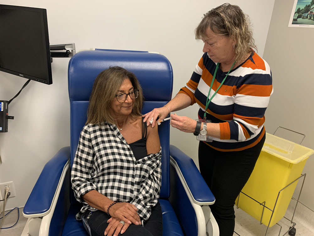 Nouritte Dayan, Administrative Agent in the Accounts Payable Department, receives her flu vaccination from Nursing Assistant Donna-Sue Kernohan during the staff vaccination clinic at CLSC Benny Farm