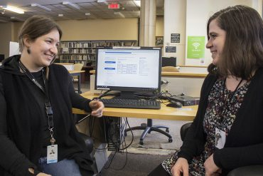 In the CIUSSS Library at the Jewish General Hospital, Medical Librarians Kendra Johnston (left) and Julia Kleinberg discuss the new web page, visible on the computer screen.
