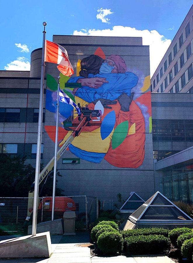 Fin août, les dernières touches ont été apportées à la fresque murale qui couvre une grande partie du mur est du pavillon G, devant l'entrée principale de l'Hôpital. La murale illustre un patient reconnaissant et un travailleur de la santé qui s'étreignent, tous deux vêtus d'équipement de protection individuelle. Des versions agrandies des feuilles illustrées dans le logo de l'HGJ tourbillonnent autour d'eux.