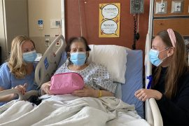 Emanuela Ciarlelli (à gauche), infirmière-chef, Division de chirurgie orthopédique, et Karine Lepage (à droite), infirmière coordinatrice clinico-administrative (intérimaire), Services chirurgicaux, remettent une trousse de soins à Yefkine Chano, une patiente de la Division de chirurgie orthopédique, âgée de 95 ans