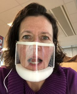 """Jackie Morrison-Visentin, a Speech Language Pathologist at the Mackay Centre School, demonstrates how she teaches a child to make the """"L"""" sound while wearing a clear mask"""