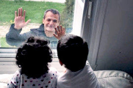 At left, Nurse Hossein Mansouri sees his children through the window of his home in May, 2020. He moved into a hotel to protect them against COVID-19. On the right, Mr. Mansouri receives a COVID-19 vaccine on Dec. 17, 2020.