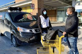 Antonin Benoît (à gauche), un employé de MultiCaf, transmet des renseignements sur la COVID-19 à l'extérieur d'un supermarché du quartier Côte-des-Neiges. La « COVID-mobile », à l'arrière-plan, diffuse des messages de santé publique dans une douzaine de langues par le biais d'un haut-parleur.