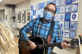 Music therapist Sam Minevich playing his guitar on the Geriatrics floor