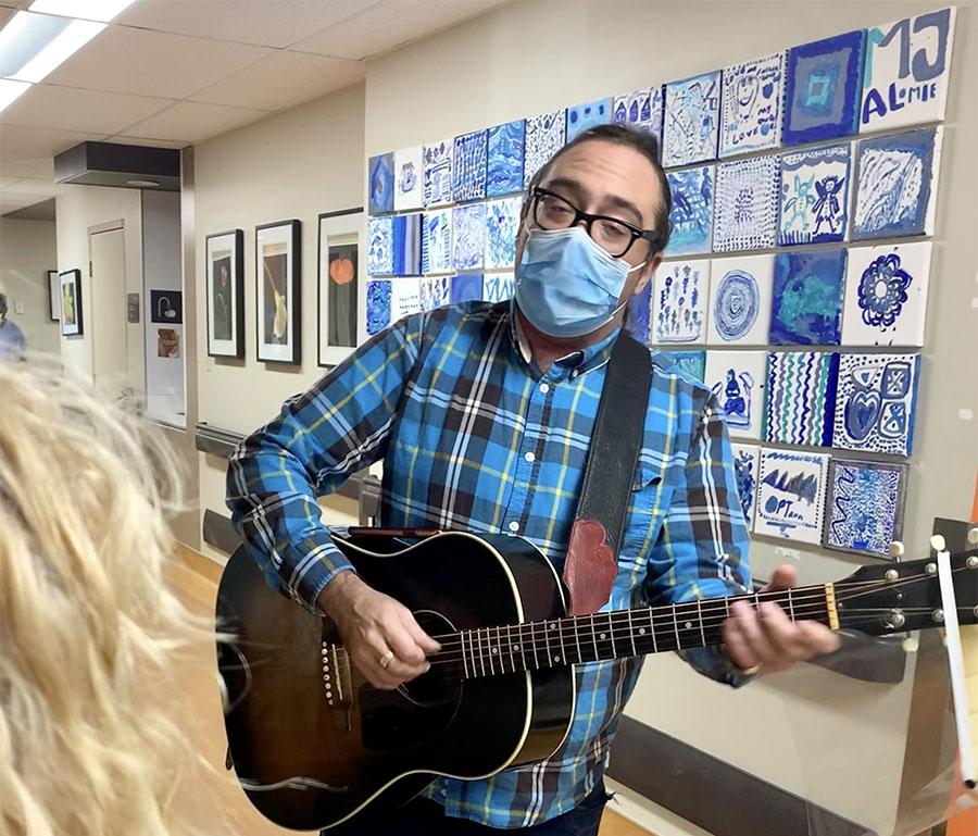 Le musicothérapeute Sam Minevich joue de la guitare à l'étage de la Gériatrie