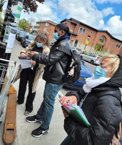 (From left): Stella Bailakis, Joël Poirier and Paris Nanas distribute posters to promote a COVID-19 vaccination pop-up clinic in Parc Extension in May.