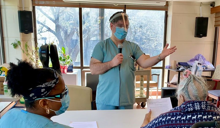 Chaplain Kosta Theofanos speaks to a resident at Saint Andrew's Residential Centre, as Service Aide Edna Bishop looks on.