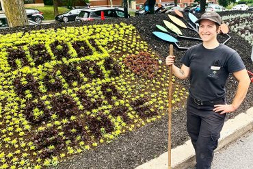 Horticultural Technician Hudson-Simone Lacharité of the Maintenance Department with the floral display she planted. It reads Merci héros de la santé, or Thank You Health Heroes.