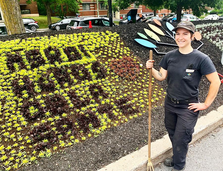 La technicienne en horticulture Hudson-Simone Lacharité du Service de maintenance devant la mosaïque florale qu'elle a planté pour écrire Merci héros de la santé.
