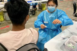 Kathleen Manalastas, a Candidate for the Profession of Nursing (CPN) who will be working at the Jewish General Hospital, administers a shot to a high-school student at the Bill-Durnan Arena vaccination site of our CIUSSS.