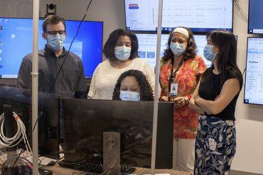 Au Centre de commandement numérique de l'HGJ, Suzette Chung (assise), responsable de la Planification des congés de l'Hôpital, et (à partir de la gauche) Matthew Wener, physiothérapeute et membre de l'équipe du Guichet d'accès aux lits de réadaptation en santé physique et soins respiratoires, Arleyne Coombs, chef des Services sociaux, Marcia Da Silva, travailleuse sociale à la direction de Santé mentale et dépendance, et Thu Hanh Ngo Nguyen, chef d'administration du programme Accès, discutent du congé ou du transfert des patients. Les écrans en arrière-plan affichent les données à jour sur l'état et les progrès des usagers des services de santé de l'HGJ et des autres installations du CIUSSS.